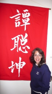 Professor Susie Lan Cassel next to Chinese characters that represent Ah Quin's name (Photo by Will Bowen)