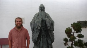 Chief Curator of Education and Exhibits Alex Stewart standing by  by statue of Confucius (Photo by Will Bowen)
