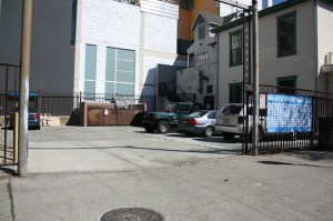 "The parking lot at 13th and J streets where a ""placemaking"" sign (at right) asks passersby ""What would you like to see here?"" (Courtesy San Diego Downtown Partnership)"