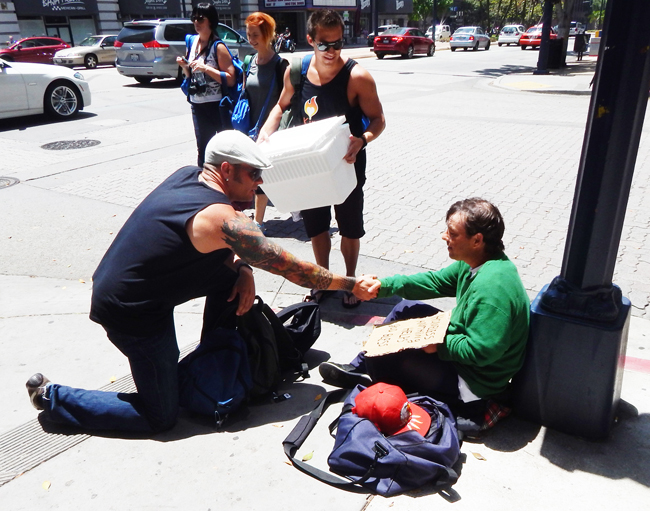 Chris Hooley of The Control Group gives a homeless man a backpack full of  necessities  (Photo by Vince Meehan)