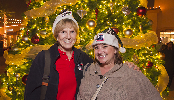 (l to r) Lynn Congemi, USO San Diego's chairman of the board with Megan Madrigal, marketing director for The Headquarters, in front of the Giving Tree, where donations for needy military families will be accepted through Dec. 24. (Photo by John Cocozza Photography)