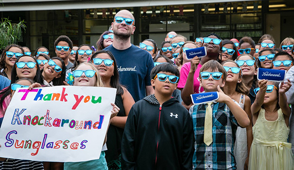 "Adam ""Ace"" Moyer, founder and CEO of Knockaround Sunglasses, surrounded by Foster Elementary School students wearing the winning ""Striker"" design, by Evan Bui (right of sign). (Photo by Mr. Bui)"