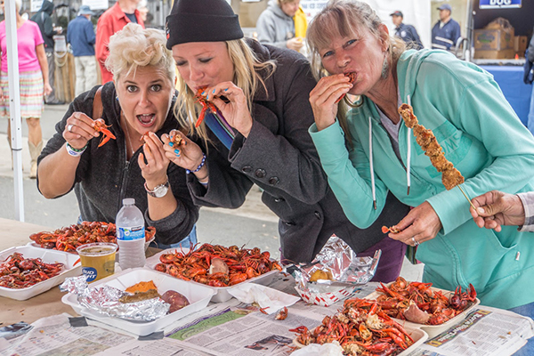 (above) Dancing at one of seven stages at Gator by the Bay (Photo by Joseph McDonald); eating some of the 10,000 pounds of crawfish (Photo by Shawn Mil/iga11)