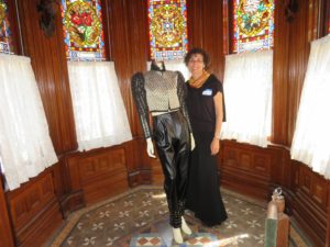 Nada Zein with one of her garments in the music room at Villa Montezuma. (Photo by Diana Cavagnaro)