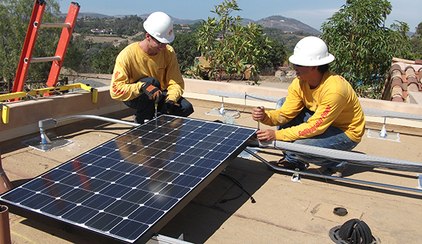 Team members install solar on a rooftop (Courtesy Sullivan Solar Power)